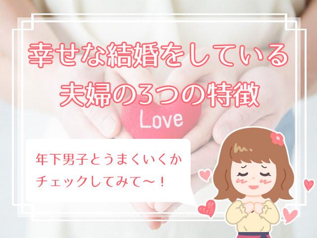 Loveとししゅうされたハート型人形を持つ手