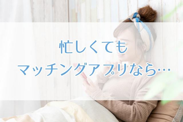 ベッドにかけてスマホを操作する女性